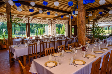 Beautifully organized event - served festive white tables ready for guests. Event in restaurant. Banquet, wedding decor, celebration. Catering and event. Wedding tables in wooden interior.
