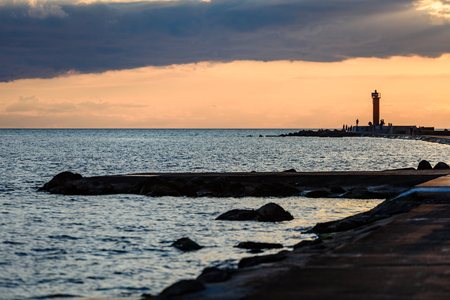 random unknown people enjoying sunset on the breakwater in the sea with lighthouse near Riga, latvia Stock Photo