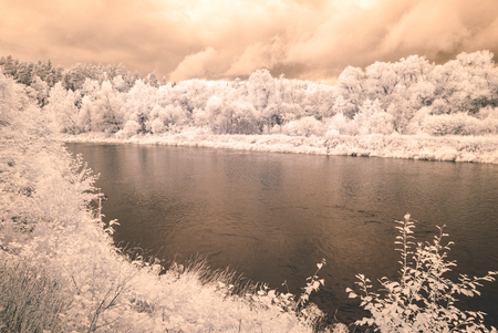 reflections in the water in countryside summer. infrared image with white trees in shore of the river - vintage effect