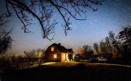 The Milky Way in night sky with stars over wooden country house at night. Latvia