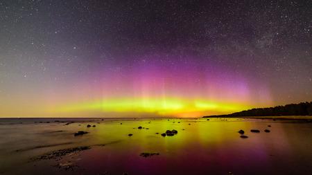 Intense northern lights (Aurora borealis) over Baltic sea. rocky beach Stock Photo