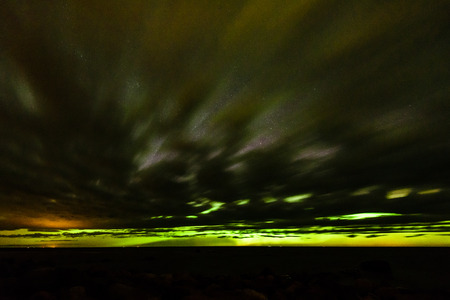 Intense northern lights (Aurora borealis) over Baltic sea. rocky beach Stock Photo