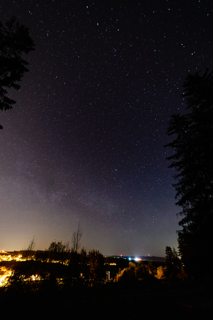 colorful milky way galaxy seen in night sky over dark trees on the horizon