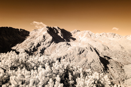 mountain panorama view from Volovec peak in Slovakia in bright sun. Infrared image colored with sun flares. invisible light series