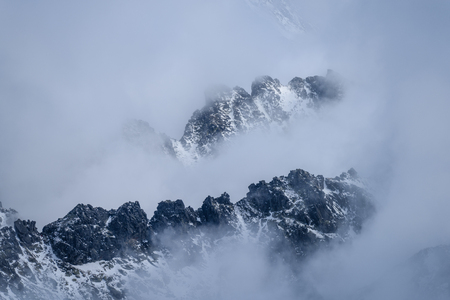 panoramic view of Tatra mountains in Slovakia covered with snow and hiding in mist. high altitude Stock Photo