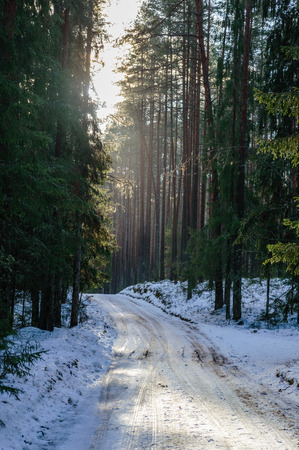 country road in winter with tyre tracks in the snow and ice Stock Photo