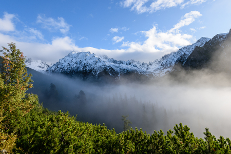 western carpathian mountain tops in  autumn covered in mist or clouds. panoramic view from a distance  in sunny day Stock Photo