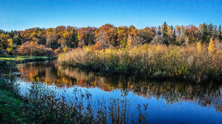 lake with water reflections in colorful autumn day with white clouds in blue sky and colored trees