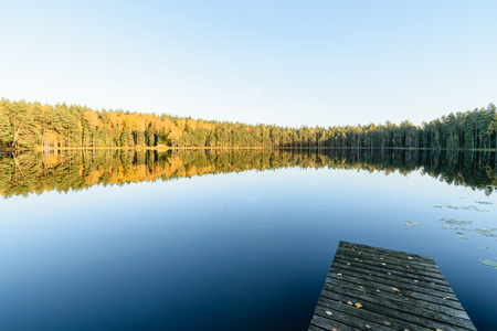 lake with water reflections in colorful autumn day with white clouds in blue sky with old wooden boardwalk Stock Photo