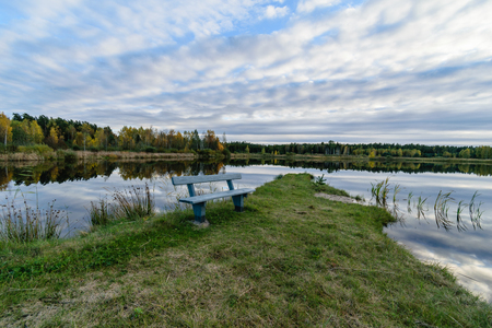 lake with water reflections in colorful autumn day with white clouds in blue sky and bench on the shore Stock Photo