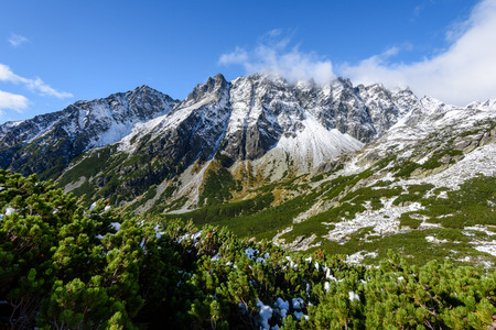slovakian carpathian mountains in autumn. hiking trail on top of the mountain. sunny day for travel. green hills with tops covered in first snow and white clouds above