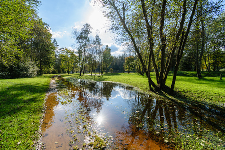 high water level in river Gauja, near Valmiera city in Latvia. summer trees surrounding and reflections of white clouds Stock Photo