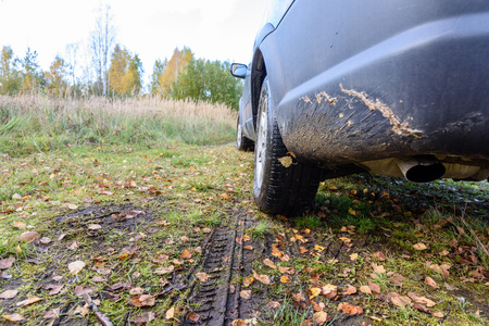Unidentified offroad vehicle in muddy meadow with autumn leaves and wet dirt