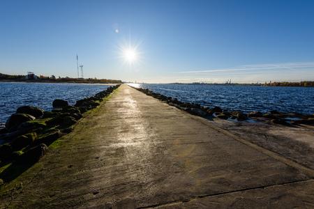 random unknown people enjoying sunset on the breakwater in the sea with lighthouse near Riga, latvia Stock Photo