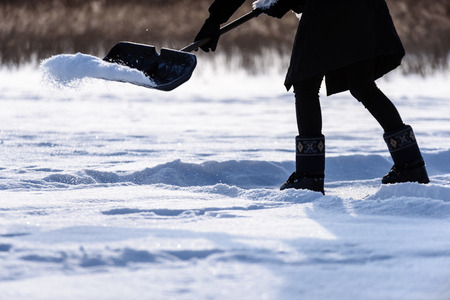 young woman in black coat cleaning ice from snow on a frozen lake to make skating ground Banque d'images