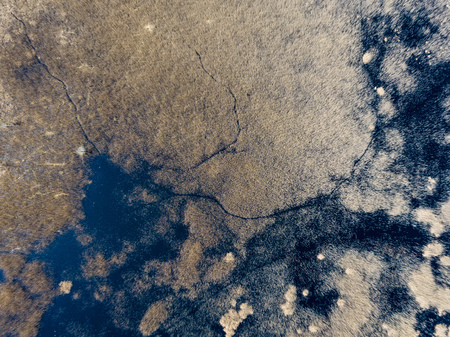 drone image. aerial view of rural area with fields and forests and swamp lake with blue water. latvia Banco de Imagens