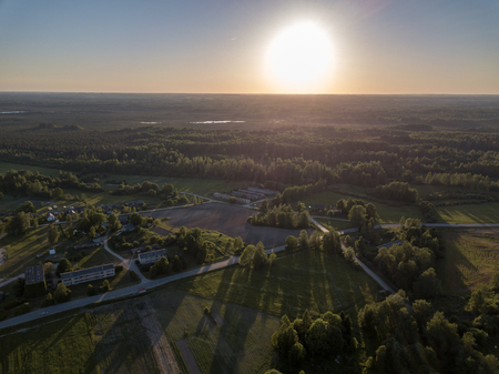 drone image. aerial view of rural sunset over forest trees with long shadows. latvia 版權商用圖片