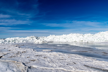 frozen lake covered with stack of ice floes and blue sky. latvia, winter Standard-Bild