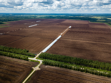 drone image. aerial view of rural area with fields of turf fuel cells development and storage in Latvia