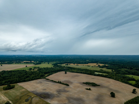 drone image. aerial view of rural area with fields and forests under dramatic storm clouds forming. summer day in latvia