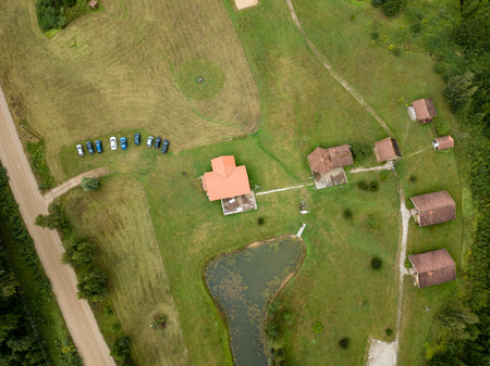 drone image. aerial view of rural area with fields and forests. camping housing rooftops. latvia