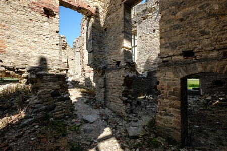 ruins of old abandoned house mansion with yellow bricks and stone in early spring in Estonia Editorial