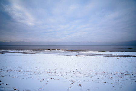 frozen dunes by the sea with ice water and snow on the beach sand