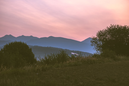 beautiful sunset in the mountains of Tatra, slovakia. hill tops with red clouds over them.  Western carpathian - vintage retro look