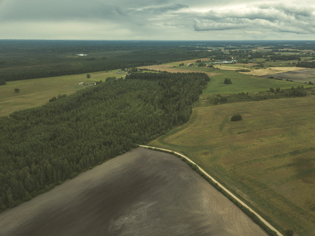 drone image. aerial view of rural area with fields and forests under dramatic storm clouds forming. summer day in latvia - vintage retro look Stock Photo