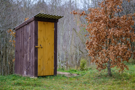 old wooden countryside toilet house with heart shaped hole in the door planks Фото со стока
