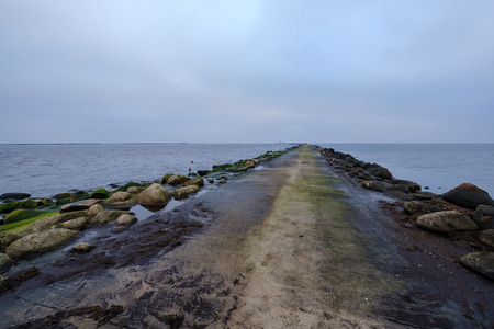 breakwater in sea with old metal railing port dock in empty autumn beach 免版税图像