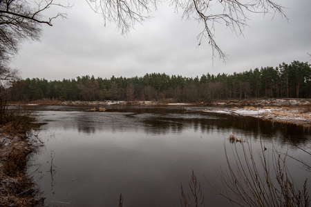 river of Gauja near Valmiera with sandstone cliffs and calm water in early winter. naked trees