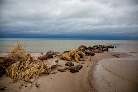 rocky coastline in Latvia with flow water in the sea and large rocks in late autumn. dull colors