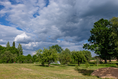storm clouds forming over the countryside and fields with roads
