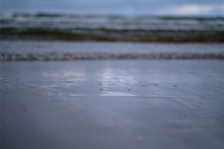 storm clouds over sea. small waves on clean white sand beach. shallow depth of field