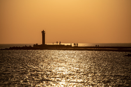 breakwater in the sea with red lighthouse at the end at the sunset with people walking by