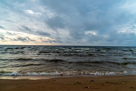 storm clouds forming over clear sea beach with rocks and clear sand. dramatic colors