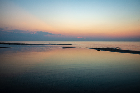 calm blue sunset over clear water in baltic sea. minimalistic image with straight horizon line and texture in water from waves