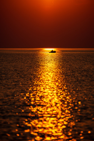dramatic red orange colored sunset over the calm sea at summer with sun way of reflections in water 写真素材