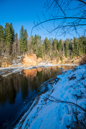 sandstone cliffs on the shore of river Gauja in Latvia. winter sunny day with ice blocks in dark water. snowy forest trees 스톡 콘텐츠 - 114955760
