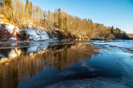 sandstone cliffs on the shore of river Gauja in Latvia. winter sunny day with ice blocks in dark water. snowy forest trees Foto de archivo - 114956247