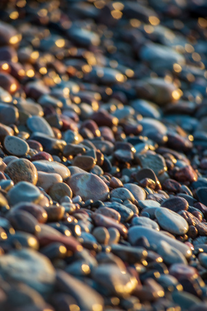 abstract details of rocky beach pebbles in sunset by the sea with foam waves