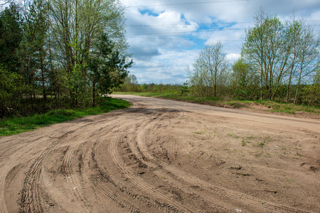 country gravel road in perspective with old and broken asphalt in spring season with poor vegetation