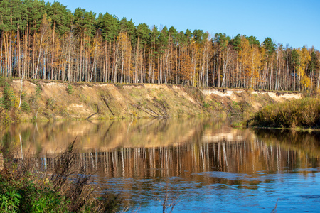 blue sky and clouds reflecting in calm water of river Gauja in latvia in autumn. walk on the shore of riverbank. clear fall day. wide angle view Foto de archivo - 116548213