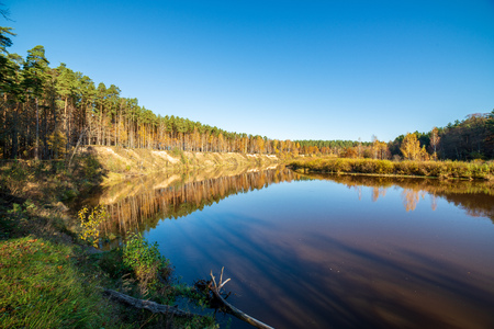 blue sky and clouds reflecting in calm water of river Gauja in latvia in autumn. walk on the shore of riverbank. clear fall day. wide angle view Foto de archivo - 116548224