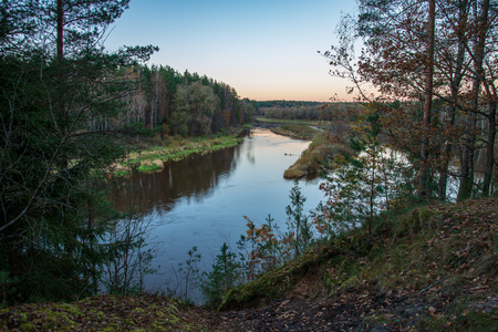 blue sky and clouds reflecting in calm water of river Gauja in latvia in autumn. walk on the shore of riverbank. clear fall day. wide angle view