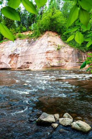 sandstone cliffs on the shore of forest river in summer sunny day with harsh shadows and trees in forest