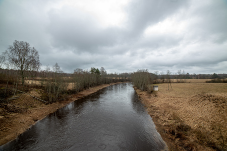 riverside landscape in latvia with dark water and dirty shore line. high water in spring with old wood and dirt
