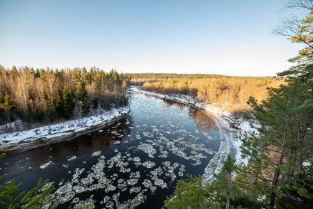 river of gauja in latvia in winter with floating ice blocks and snow covered shores