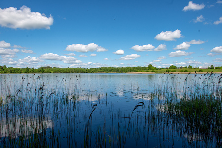 blue sky and cloud reflections in countryside lake in summer with boat and wooden boardwalk romance Archivio Fotografico